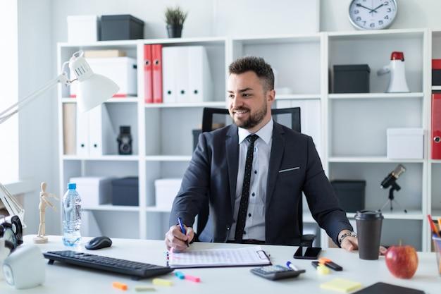 Mężczyzna siedzi w biurze przy stole, trzymając w ręce szklankę kawy i długopis i pracując z dokumentami.