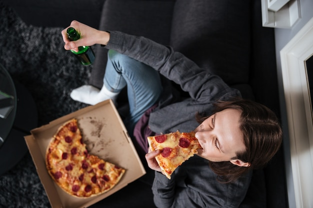 Mężczyzna siedzi w domu w domu jedzenie pizzy