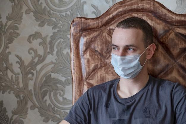 Mężczyzna siedzi w domu w medycznej masce. kwarantanna
