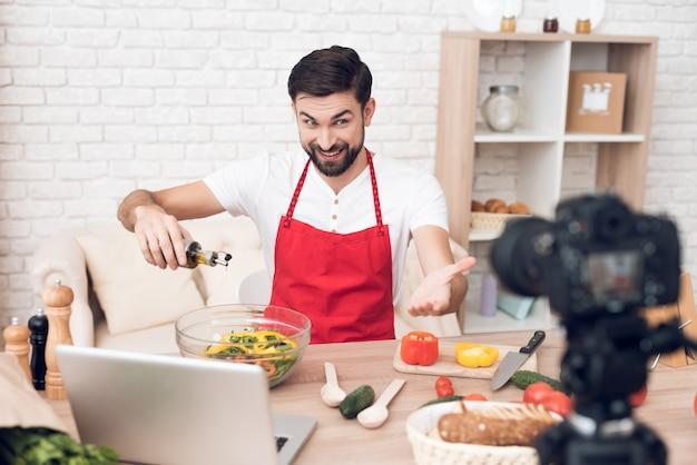 Mężczyzna siedzi w fartuchu i gotuje przed kamerą.
