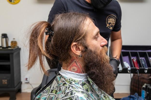 Mężczyzna siedzi w fotelu fryzjerskim.