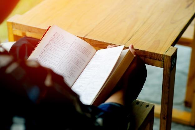 Mężczyzna siedzi w fotelu vintage przed swoim domem w dzień odpoczynku poczytaj książkę i zrelaksuj się. niewyraźne tło. efekt filmu poziomego. koncepcja czytania książek w celu zwiększenia samopoznania.