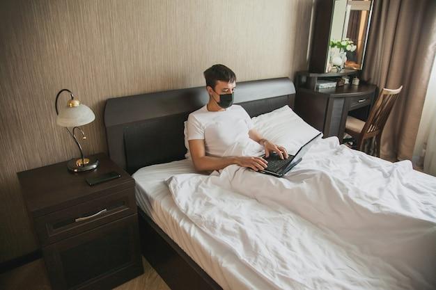 Mężczyzna siedzi w łóżku w swojej sypialni i pracuje przy laptopie z maską medyczną na twarzy