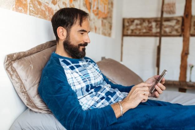Mężczyzna siedzi w łóżku zrelaksowany w domu na telefon komórkowy