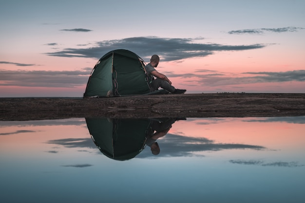 Mężczyzna siedzi w namiocie i podziwia zachód słońca
