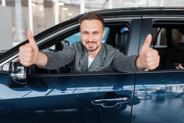 Mężczyzna siedzi w nowym samochodzie i pokazuje kciuki do góry