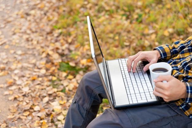 Mężczyzna siedzi w parku i pracuje na laptopie na zewnątrz ręce piszące na klawiaturze i trzymające kubek kawy