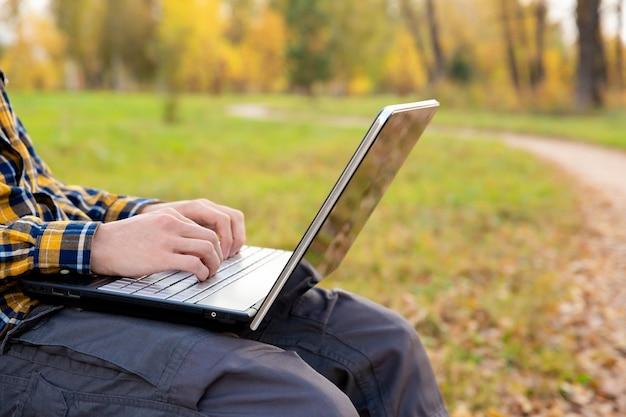 Mężczyzna siedzi w parku i pracuje przy laptopie na zewnątrz ręce piszące na klawiaturze