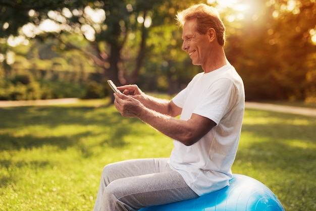Mężczyzna siedzi w parku na niebieskim miskę do jogi.
