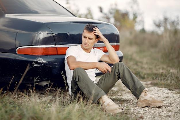 Mężczyzna siedzi w pobliżu uszkodzonego samochodu