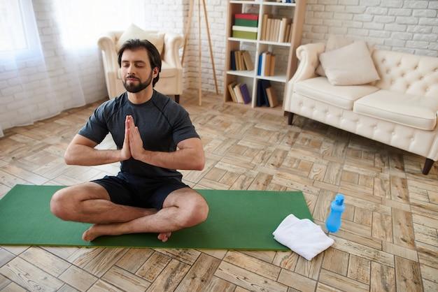 Mężczyzna siedzi w pozycji lotosu na zielonym dywanie.