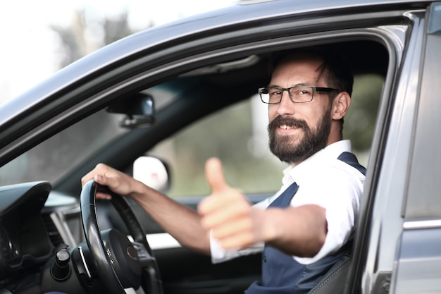 Mężczyzna siedzi w samochodzie i pokazuje kciuk do góry