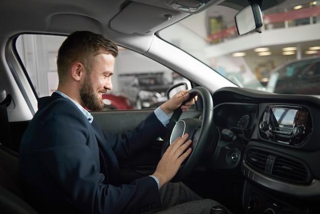 Mężczyzna siedzi w samochodzie, trzymając się za ręce na kierownicy.