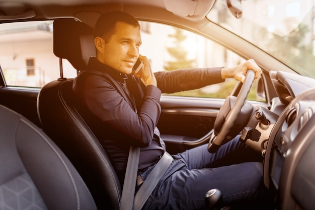 Mężczyzna siedzi w samochodzie. wnętrze pojazdu. biznesmen jazdy
