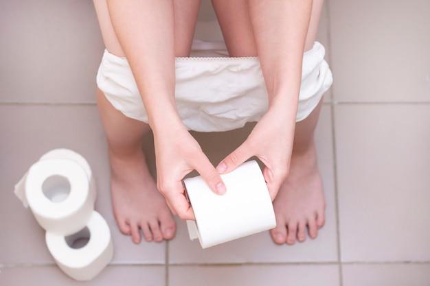 Mężczyzna siedzi w toalecie. zaparcia lub biegunka. papier toaletowy na podłodze. mężczyzna trzyma papier toaletowy w dłoniach.