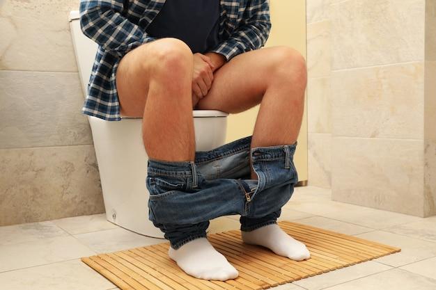 Mężczyzna siedzi w toalecie ze spuszczonymi spodniami
