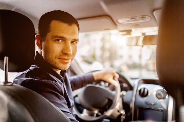 Mężczyzna siedzi we wnętrzu samochodu, patrzy w kamerę i uśmiecha się. koncepcja transportu.