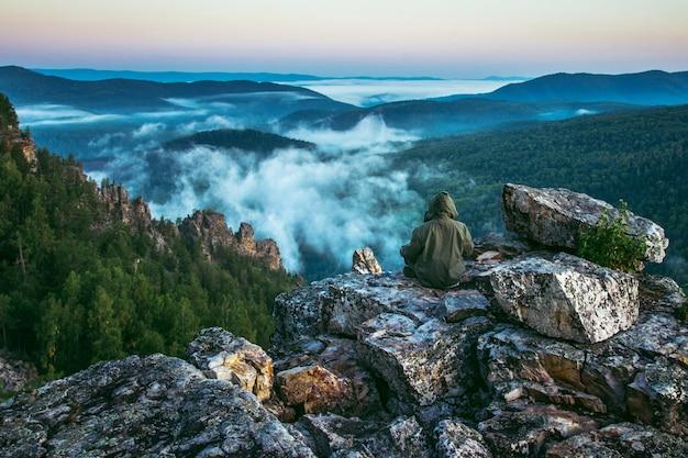 Mężczyzna siedzi z powrotem na szczycie gór i cieszy się, aby zobaczyć piękny widok krajobrazu skał i mgły nadchodzących w letni poranek