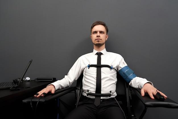 Mężczyzna siedzi z przymocowaniem czujników na palcach i ciele.
