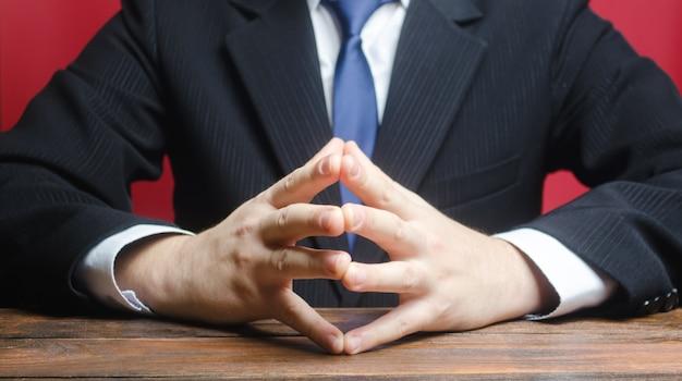 Mężczyzna siedzi z rękami w zamku. rozwiązywanie konfliktów, poszukiwanie kompromisu