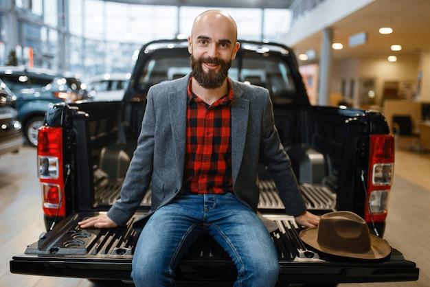 Mężczyzna siedzi z tyłu nowego pickupa w salonie samochodowym. klient w salonie samochodowym, mężczyzna kupujący transport, firma dealera samochodowego dealer