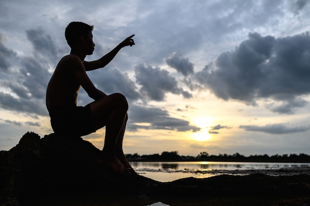 Mężczyzna siedział na podstawie drzewa, kładąc ręce podczas zachodu słońca.