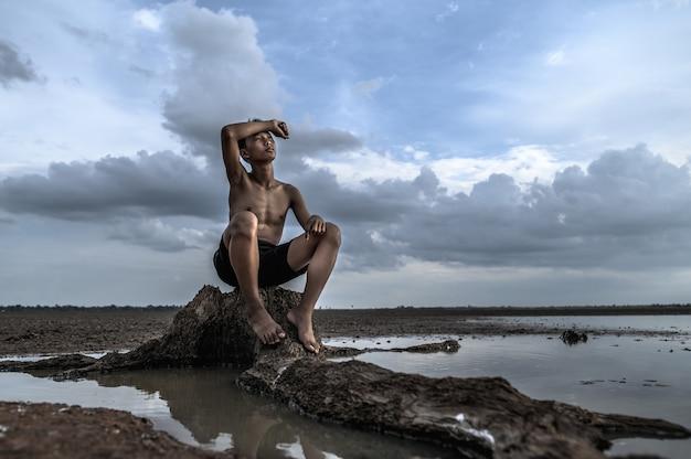Mężczyzna siedział na podstawie drzewa, z dłonią na czole i otoczony wodą.