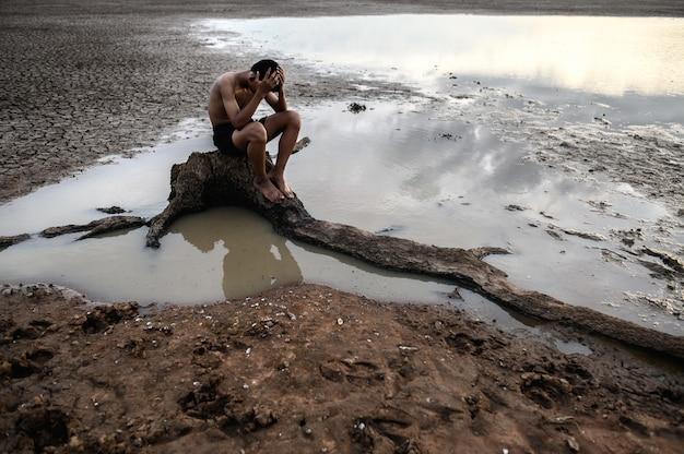Mężczyzna siedział pochylony na kolanach i położył ręce na głowie, na podstawie drzewa i otoczony wodą.