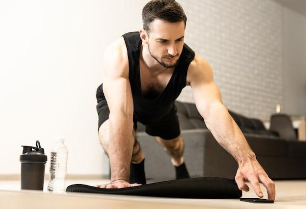 Mężczyzna sięga po telefon, aby zmienić muzykę w telefonie na sport. trening na macie do jogi w domu. poranne ćwiczenia z muzyką. zajęcia sportowe podczas kwarantanny.