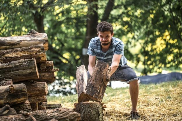 Mężczyzna sieka drewno siekierą