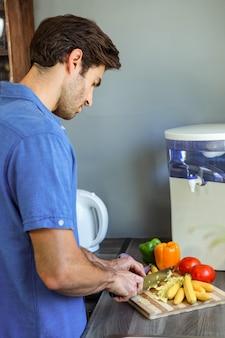 Mężczyzna sieka warzywa przy kuchennym kontuarem