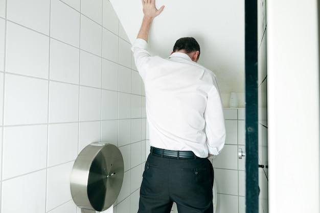 Mężczyzna sika w toalecie