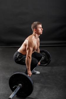 Mężczyzna siłacz robi ćwiczenia fitness ze sztangą