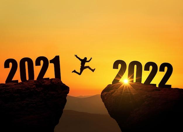 Mężczyzna skaczący na klifie 2022 nad przepaścią o niesamowitym zachodzie słońca. koncepcja noworoczna. symbol rozpoczęcia i powitania szczęśliwego nowego roku 2022. ludzie wchodzą w rok 2022, kreatywny pomysł