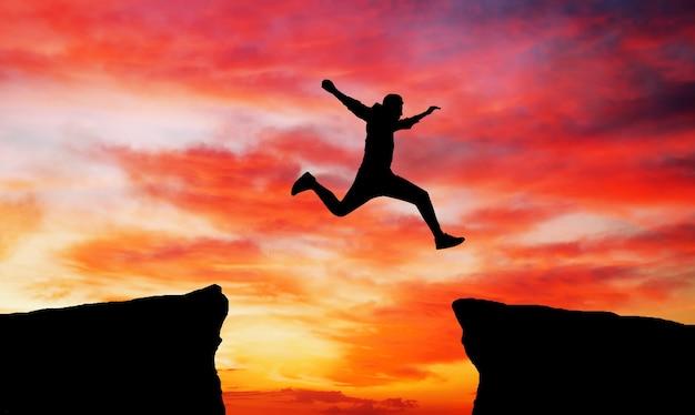 Mężczyzna skaczący przez szczelinę z jednej skały do drugiej. człowiek przeskakując skały z luką na tle zachodu słońca ognisty. element projektu.