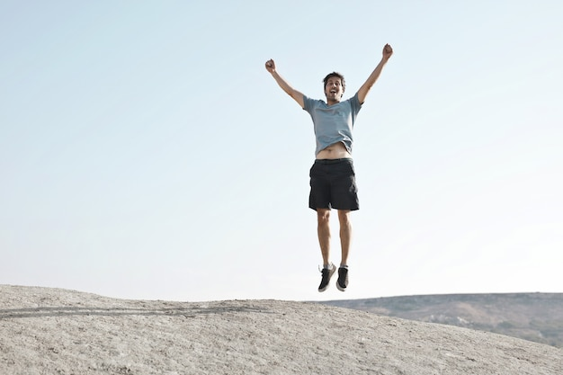 Mężczyzna skaczący z podniesionymi rękami, przedstawiający wolność lub sukces
