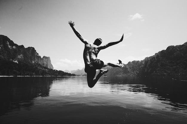 Mężczyzna skaczący z radości nad jeziorem