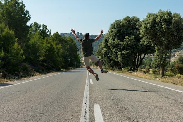 Mężczyzna skacze na pustej drodze. obieżyświat