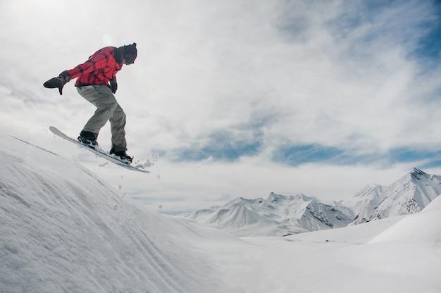 Mężczyzna skacze na snowboardzie na ośnieżone szczyty górskie