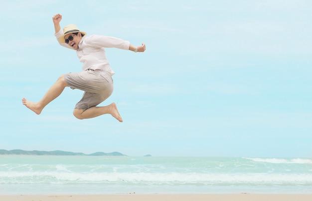 Mężczyzna skacze szczęśliwy podczas wakacje przy morze plażą tajlandia