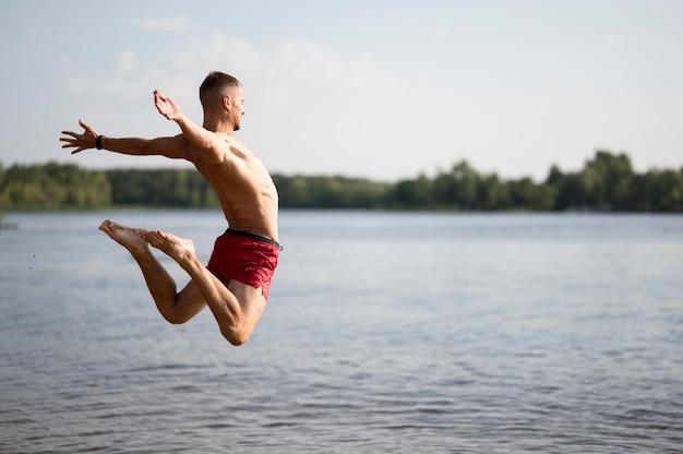 Mężczyzna skacze w jeziorze