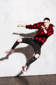Mężczyzna skacze w kraciastą koszulę i podarte dżinsy