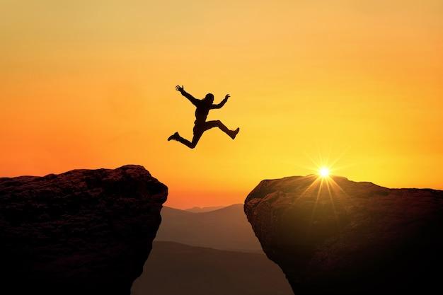 Mężczyzna skacze z klifu na klif nad przepaścią o zachodzie słońca, kreatywny pomysł. koncepcja sukcesu i ryzyka