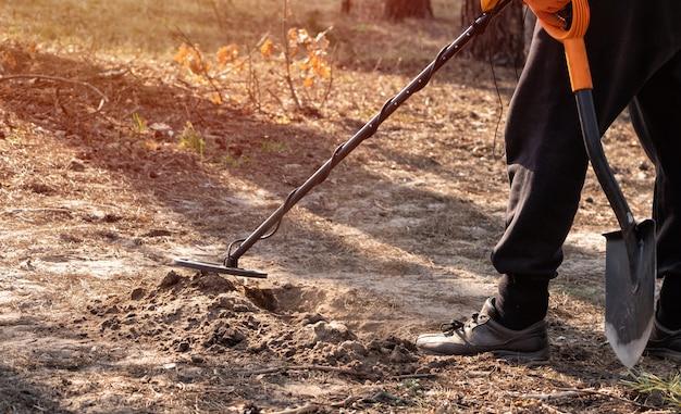 Mężczyzna skanuje wykopaną dziurę w lesie wykrywaczem metalu i łopatą w dłoniach