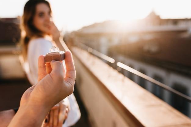 Mężczyzna składa propozycję małżeństwa dziewczynie stojącej na dachu w słoneczny dzień