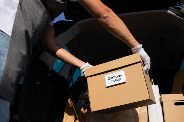 Mężczyzna składający zamówienie w bagażniku samochodu
