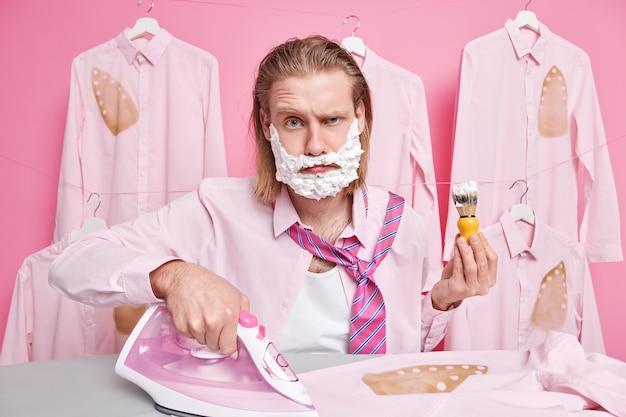 Mężczyzna skoncentrowany na prasowaniu i goleniu pozach w garderobie prasuje koszulę ubiera się na randkę zaangażowany w prace domowe ma dużo pracy podczas snu praca