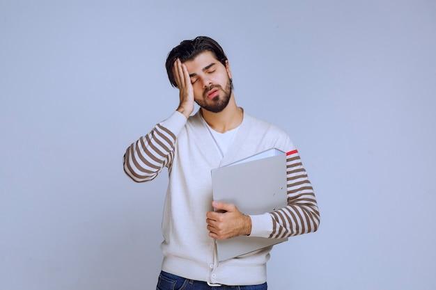 Mężczyzna skończył projekt, trzyma teczkę i wygląda na śpiącego, ponieważ jest zmęczony.