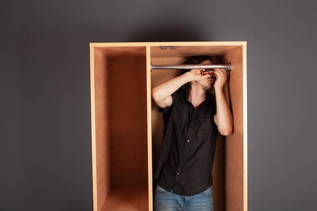 Mężczyzna skręca śrubokrętem rurę do wieszaka w szafie.