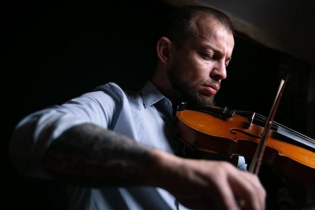Mężczyzna skrzypek gra muzykę na skrzypcach.